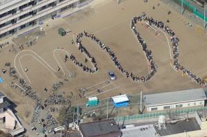 Efter tsunamin: Människor som köar för vatten vid en skola i Sendai, Japan.